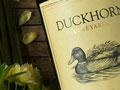 Detail of Duckhorn Merlot bottle with yellow flowers in bckground
