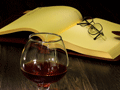 detail wine glass on table with pair of eyeglasses on open book pages