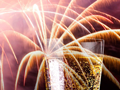 Detail of non-vintage Champagne glass against fireworks display